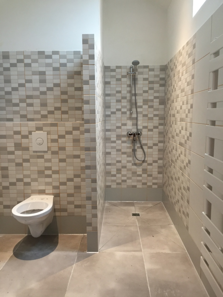 De betegelde doucheruimte met ook een Grohe inbouwtoilet.